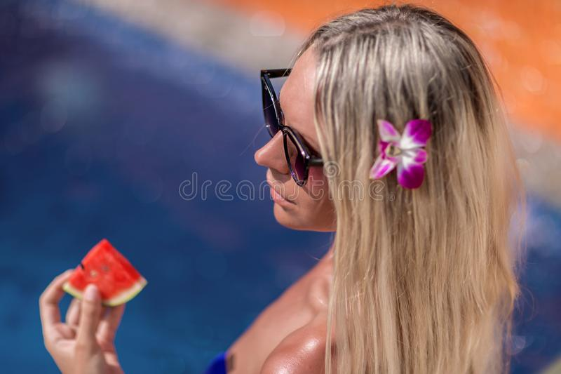 Young slim blonde woman with long hair in sunglasses eat watermelon and suntan near swimming pool. Young slim blonde woman with long hair in sunglasses eat stock photo