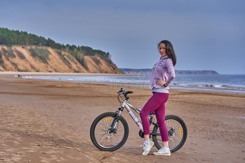 Young slim brunette woman on a bike ride on the sandy shore of a large river. Cloudy summer day royalty free stock images