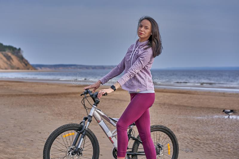 Young slim brunette woman on a bike ride on the sandy shore of a large river. Cloudy summer day stock image