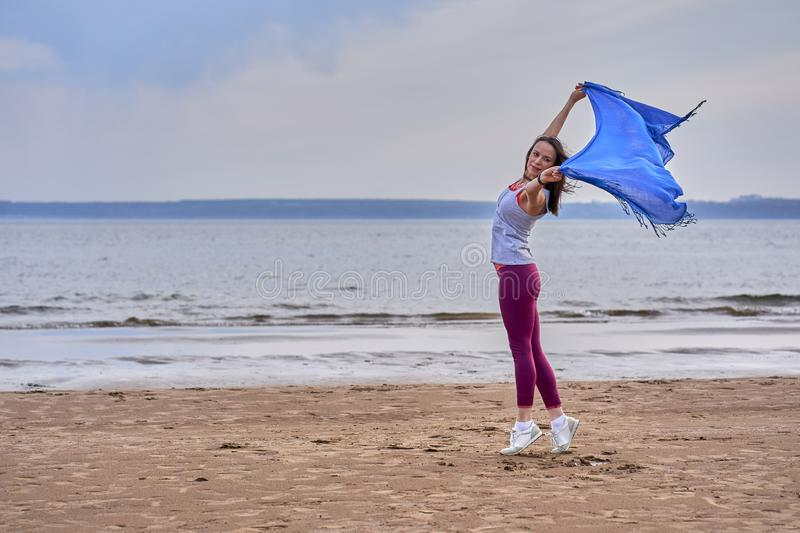 Young slim brunette woman in sportswear doing sport dancing with a blue scarf. A woman is engaged on the sandy shore of a large ri. Ver. Cloudy summer morning royalty free stock images