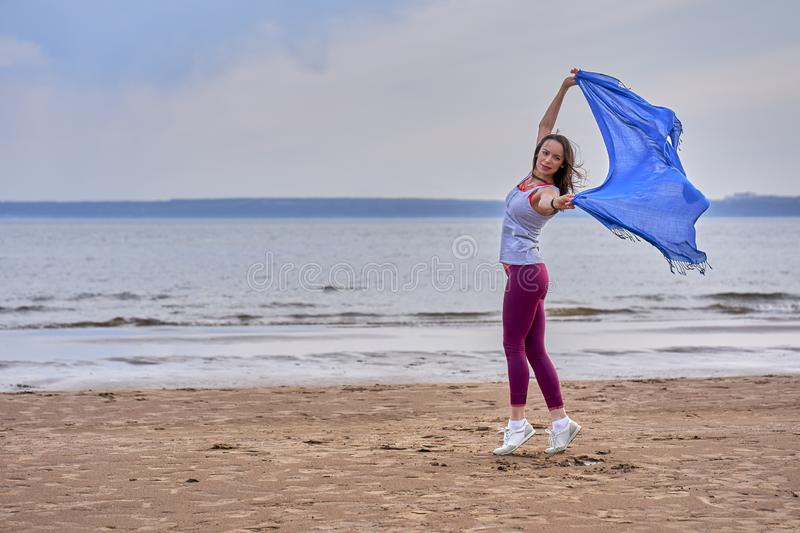 Young slim brunette woman in sportswear doing sport dancing with a blue scarf. A woman is engaged on the sandy shore of a large ri. Ver. Cloudy summer morning royalty free stock photo