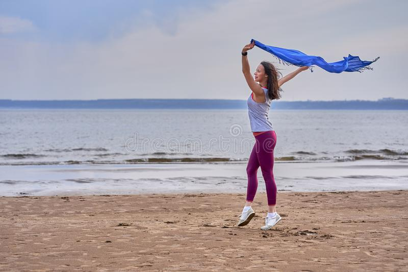 Young slim brunette woman in sportswear doing sport dancing with a blue scarf. A woman is engaged on the sandy shore of a large ri. Ver. Cloudy summer morning stock images