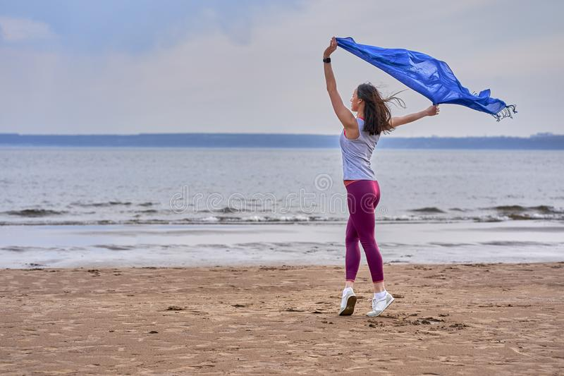 Young slim brunette woman in sportswear doing sport dancing with a blue scarf. A woman is engaged on the sandy shore of a large ri. Ver. Cloudy summer morning stock photos