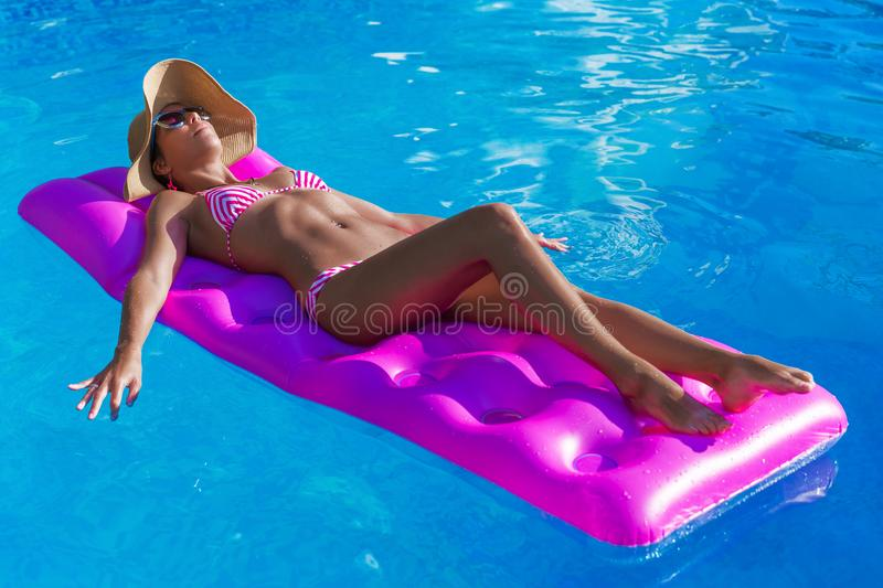 Young slim brunette woman in straw hat gets suntan on an air mat stock photography