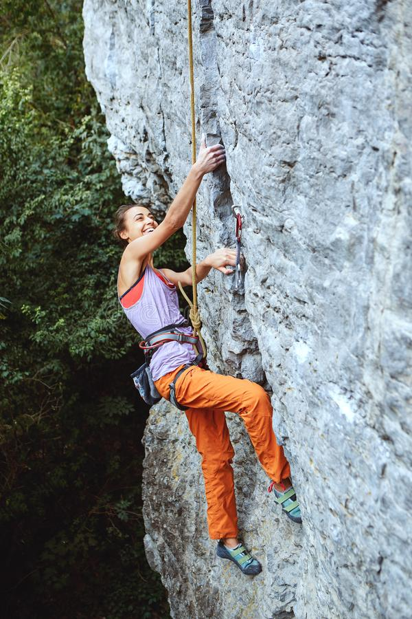 Young slim female rock climber climbing on the cliff stock images