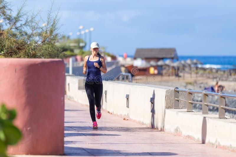 Young slim female runner near the sea jogging in the morning royalty free stock image
