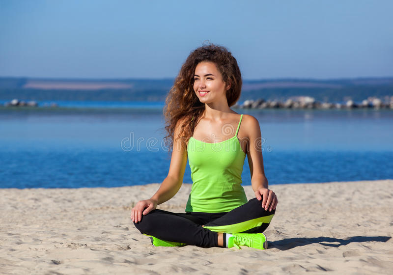 Young slim girl with curly hair in black and light green tracksuit sitting after a workout in the sand on the seashore. royalty free stock photos
