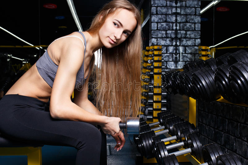 Young slim girl doing biceps curl with dumbbels. Young slim girl doing biceps curl exercise with dumbbels in the gym. Fitness woman workout with weights royalty free stock photos