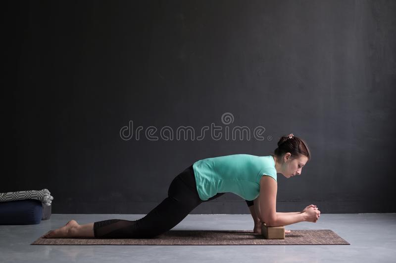 Young slim girl, doing horse rider exercise, anjaneyasana pose, working out. royalty free stock photos