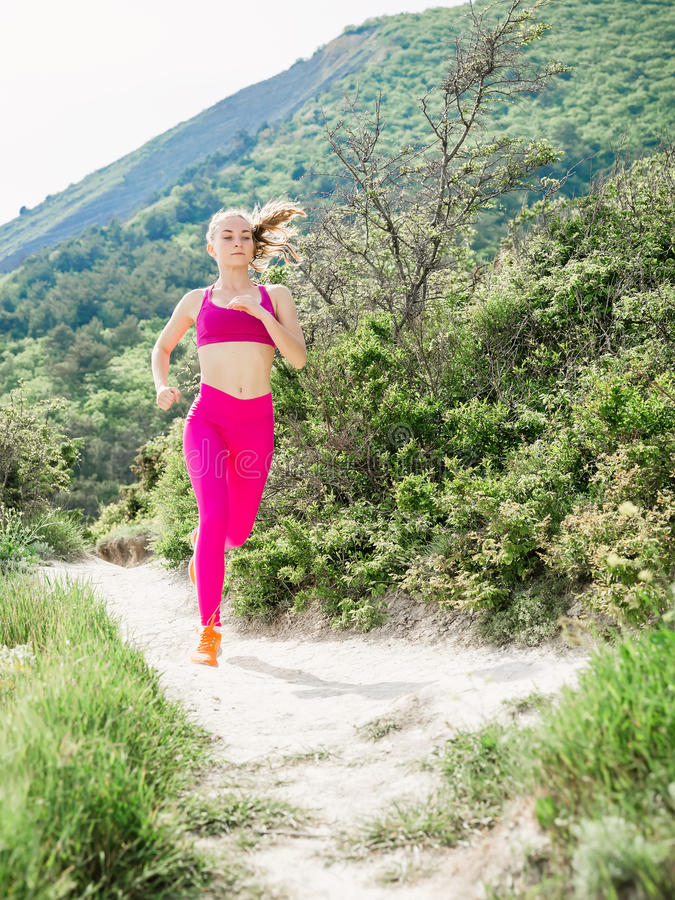 Young slim girl is running in outdoors. Sporty young woman royalty free stock image