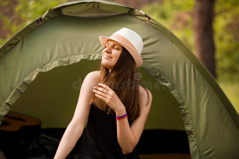 Young slim hiker woman sitting at small tourist tent enjoying beautiful nature forest on bright summer morning. stock photos
