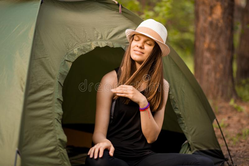 Young slim hiker woman sitting at small tourist tent enjoying beautiful nature forest royalty free stock photos