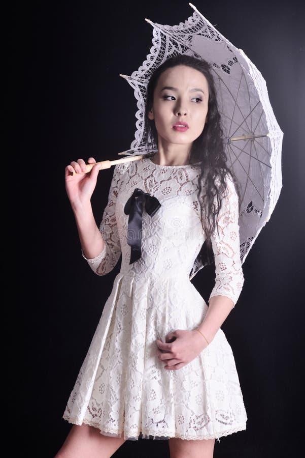 Young slim model in light summer dress with a filigree umbrella posing in studio. Black background. Young slim model in light summer dress with a filigree stock photo