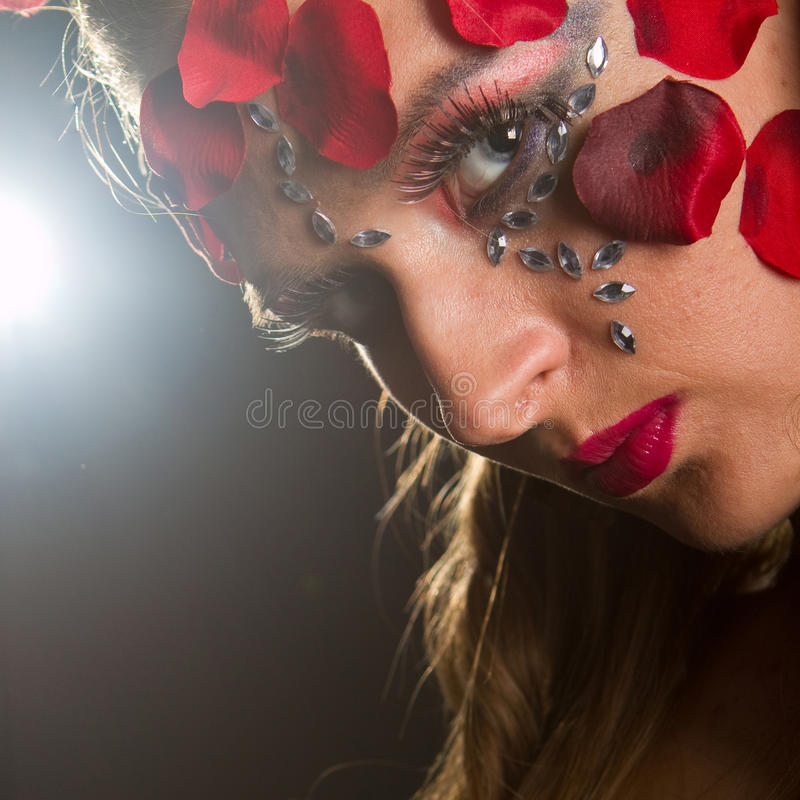 Young slim model with makeup. Young stylish fresh young model with an extreme red makeup and roses stock photos