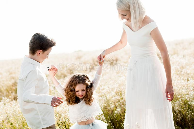 Young slim mother plays with her two children in a daisy field royalty free stock image