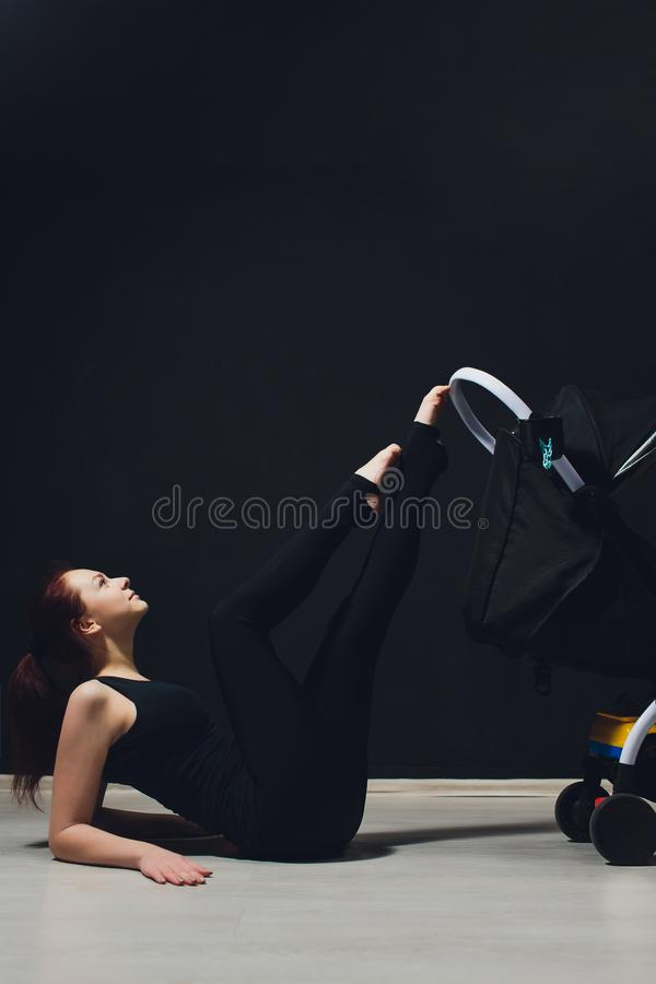 Young slim mother with a pram. young mother raises her leg, acrobatics, gymnastics, sports. royalty free stock photography