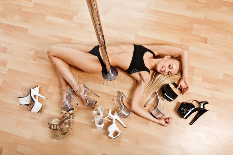 Young slim pole dance blond woman lies on floor near pool. Young slim pole dance woman in poledance class in gym royalty free stock photography