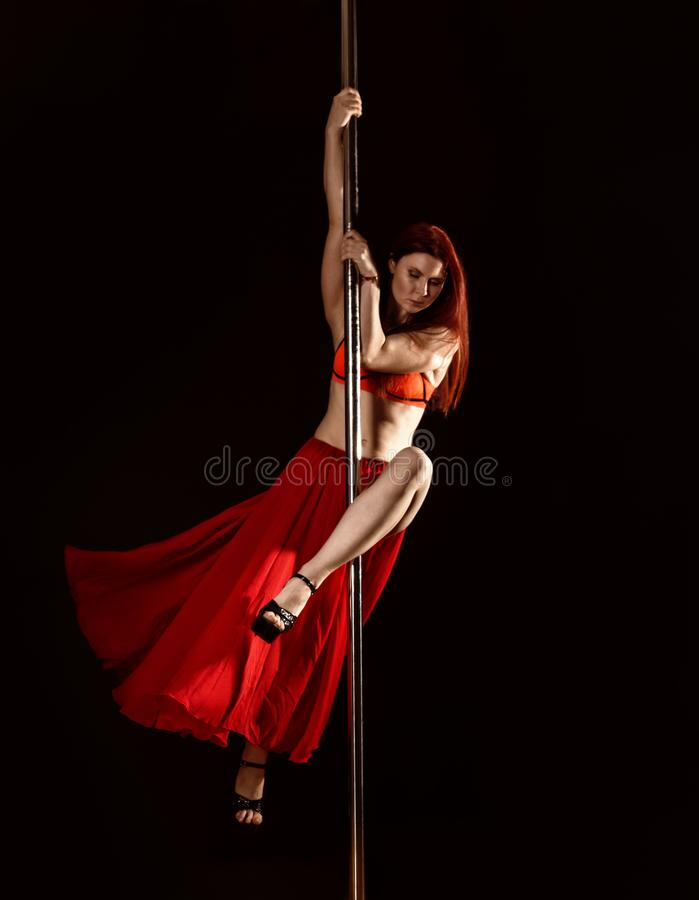 Young redhead athletic pole dance girl in a red dress on a black studio background royalty free stock photo
