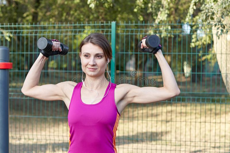 Young slim and sporty woman in bright sportswear trains with dumbbells for biceps at outdoor sportground. White earphones, protect stock photo