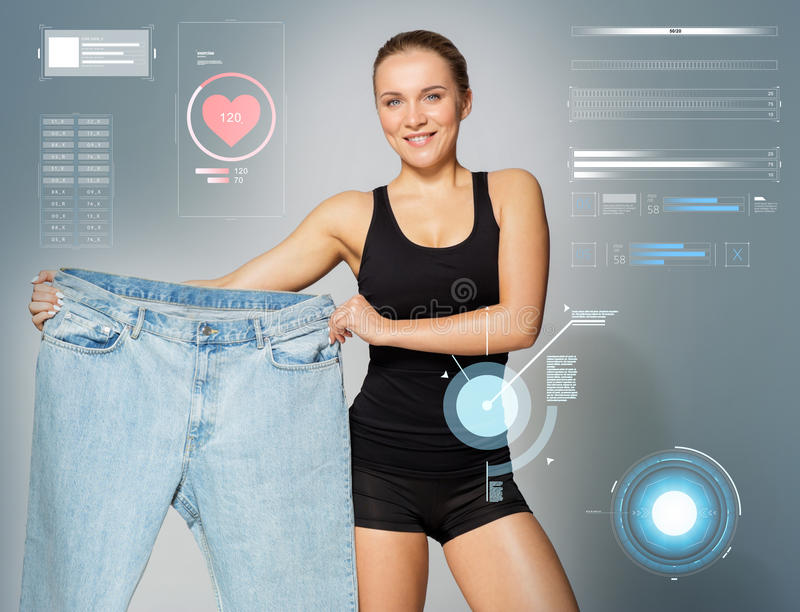Young slim sporty woman showing large size pants stock photography