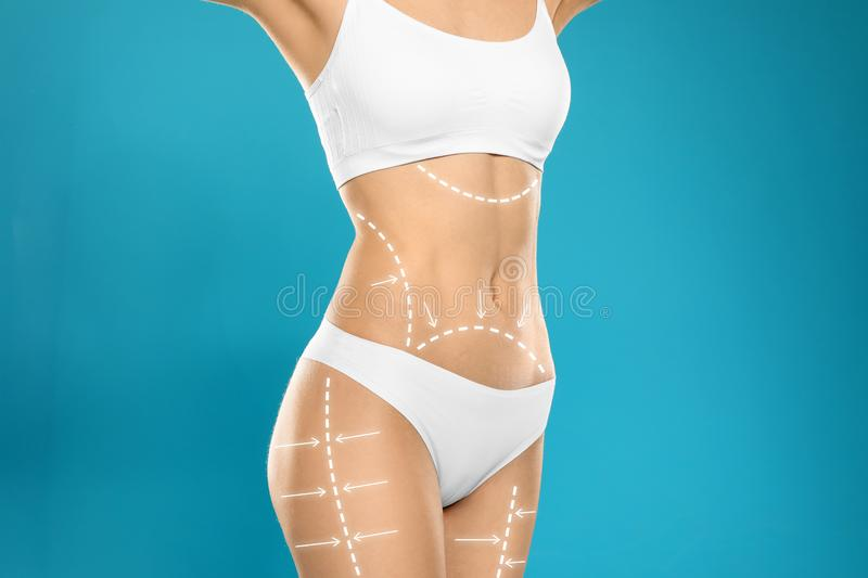 Young slim woman with arrows on body against color background. Beauty and health concept royalty free stock photos
