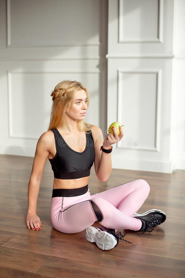 Young slim woman with an athletic body long blonde hair, dressed in a pink sports top and leggings, sits in a bright. Yoga room with a large panoramic window royalty free stock photography