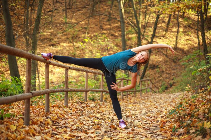 Young slim woman doing fitness exercise stretching in autumn forest park, sport and healthy lifestyle royalty free stock photo