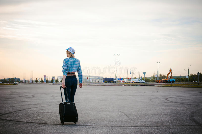 Young slim woman dressed in blue checked shirt, cap and jeans, Will depart at dawn on summer day on freedom trip with black travel stock photo