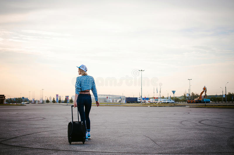 Young slim woman dressed in blue checked shirt, cap and jeans, Will depart at dawn on summer day on freedom trip with black travel. Suitcase stock photography