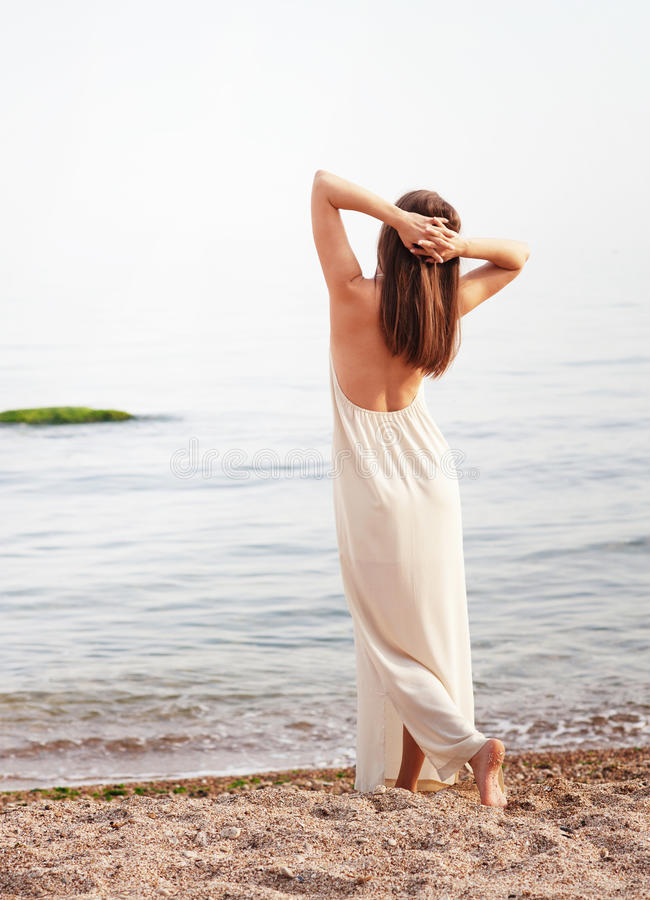 Young slim woman dressed in long white dress with open back, relaxed standing back royalty free stock photography