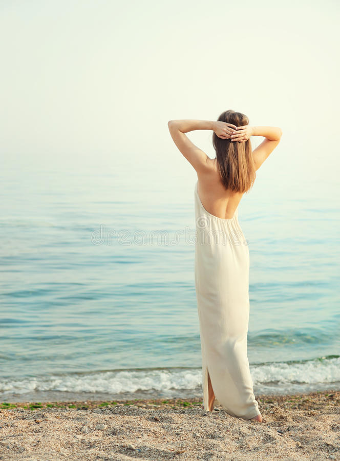 Young slim woman dressed in long white dress with open back, standing back with hands behind head. royalty free stock photo