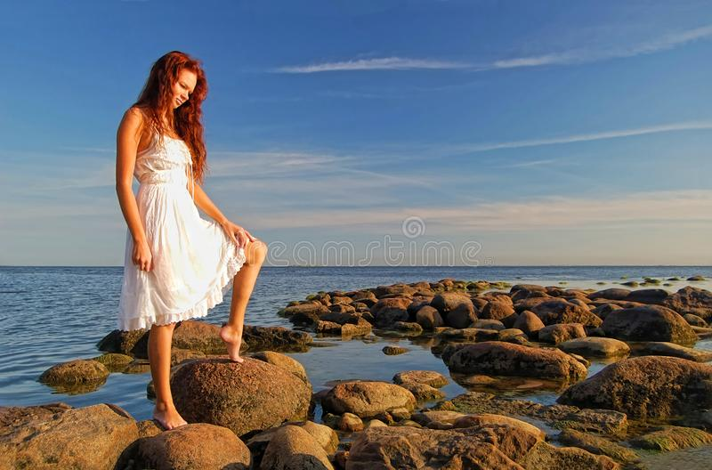 Young slim woman dressed in white sundress stock photography