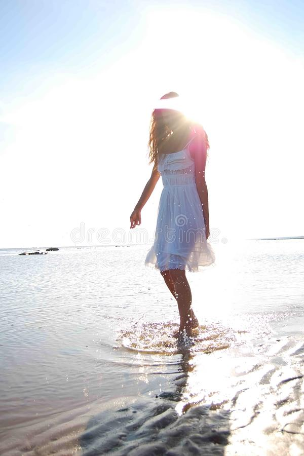 Young slim woman dressed in white sundress royalty free stock image