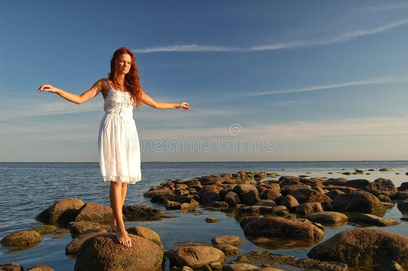 Young slim woman dressed in white sundress royalty free stock images