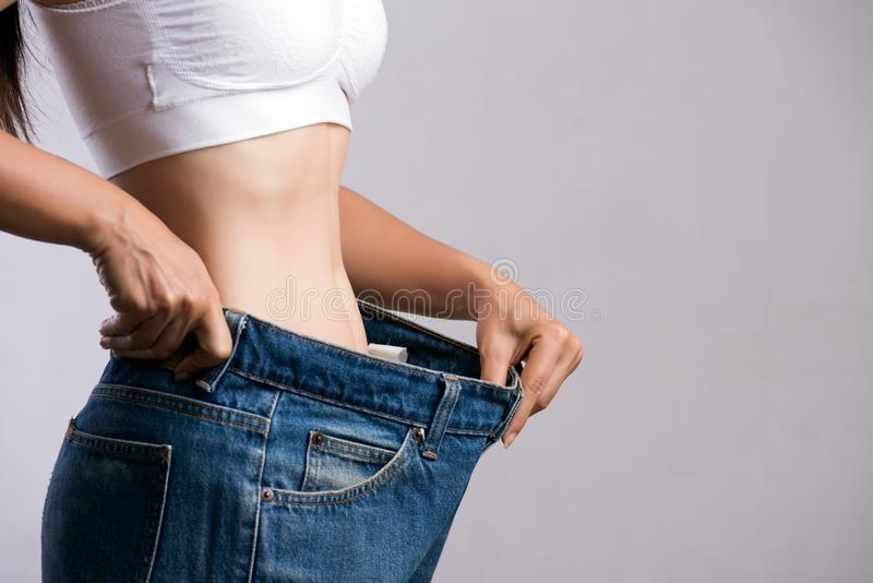 Young slim woman in oversized blue jeans. Fit woman wearing too large pants. Healthcare and woman diet lifestyle concept to reduce. Belly and shape up healthy stock images