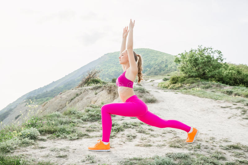 Young slim woman with perfect body is doing exercises at outdoor royalty free stock photography