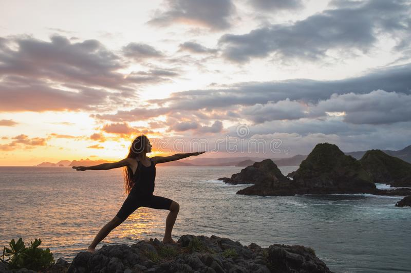 Young slim woman practicing yoga at sunset with beautiful ocean mountain view. Young slim woman practicing yoga at sunset with beautiful ocean and mountain view royalty free stock images