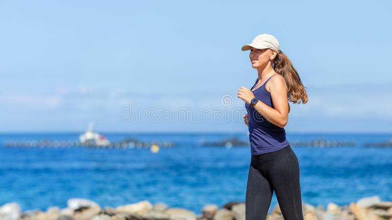 Young slim woman running near sea in the morning stock photography