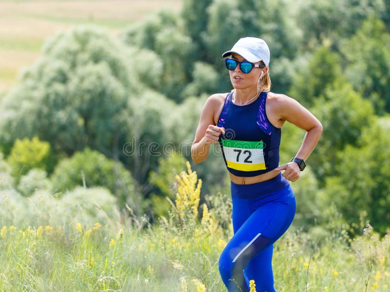 Young slim woman running trail race contest royalty free stock photo