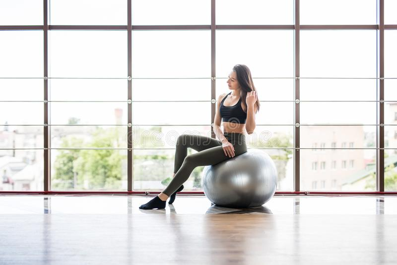 Young slim Woman in sportswear exercising her abs on a Pilates ball of fitball close up at gym. Fitness concept stock image