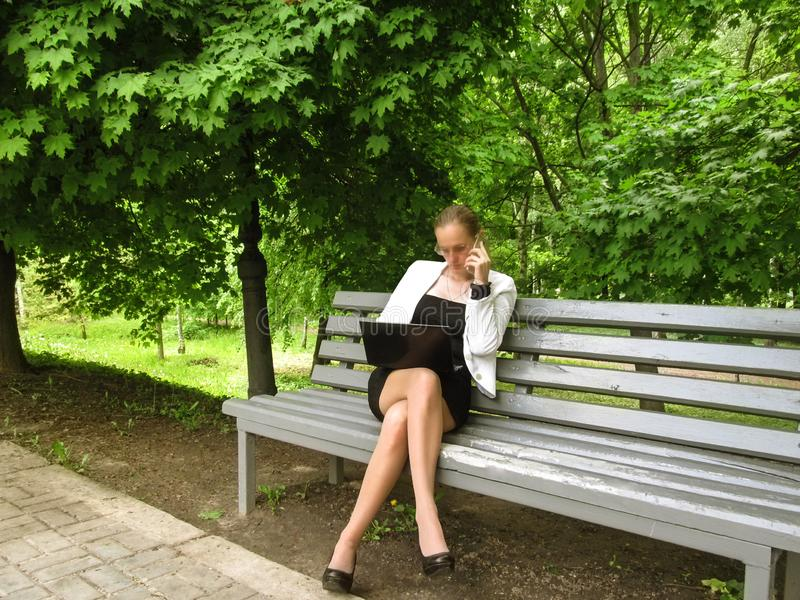 Young slim woman talking on the phone and looking into the laptop while sitting on a bench in the park. Cute adult girl in a stock image