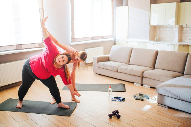Young slim woman help overweight plus size model exercising. Standing in living room and stretching up and down. Hard royalty free stock photography