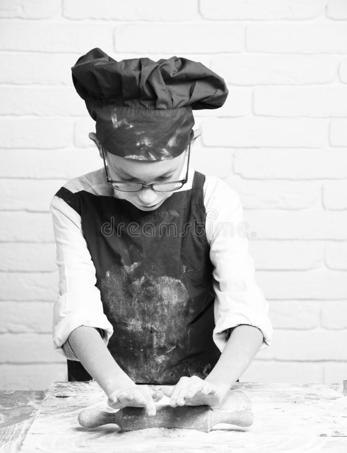 Young small boy cute cook chef in red uniform and hat on stained face flour with glasses standing near table holding. Rolling pin and cooking on white brick royalty free stock images