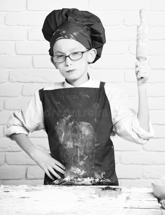 Young small boy cute cook chef in red uniform and hat on stained face flour with glasses standing near table with. Rolling pin on white brick wall background stock photo