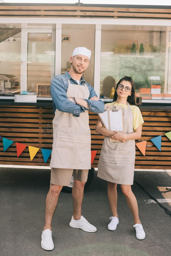 Young small business owners in aprons standing with crossed arms and smiling at camera. Near food truck stock image