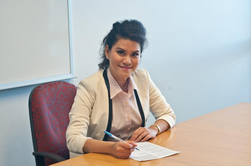 Business woman signing contract agreement in office. Young smart Asian business woman is smile while signing contract agreement in office royalty free stock photography