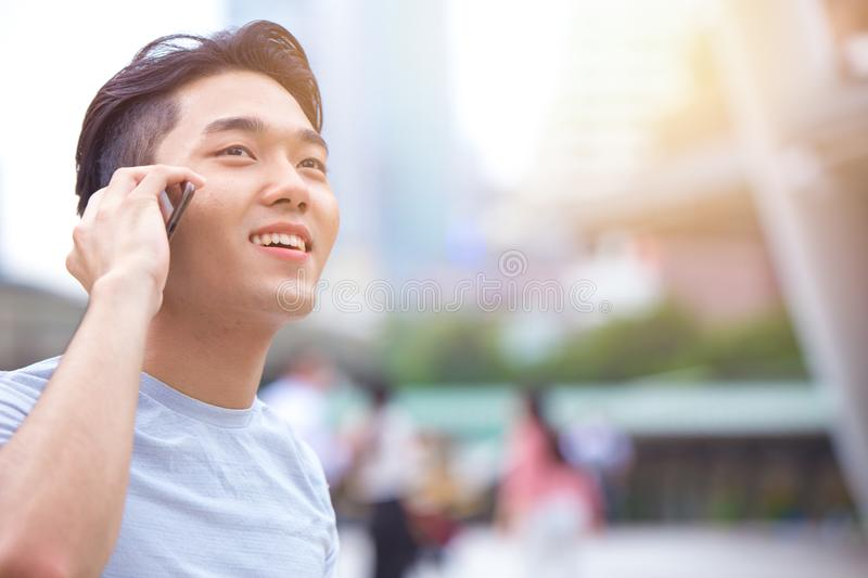 Young smart asian male teen calling phone call royalty free stock photos