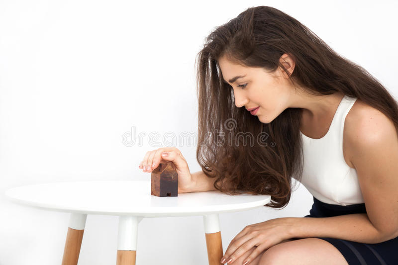 Young and smart beautiful Caucasian woman protecting and taking care of miniature house stock photos