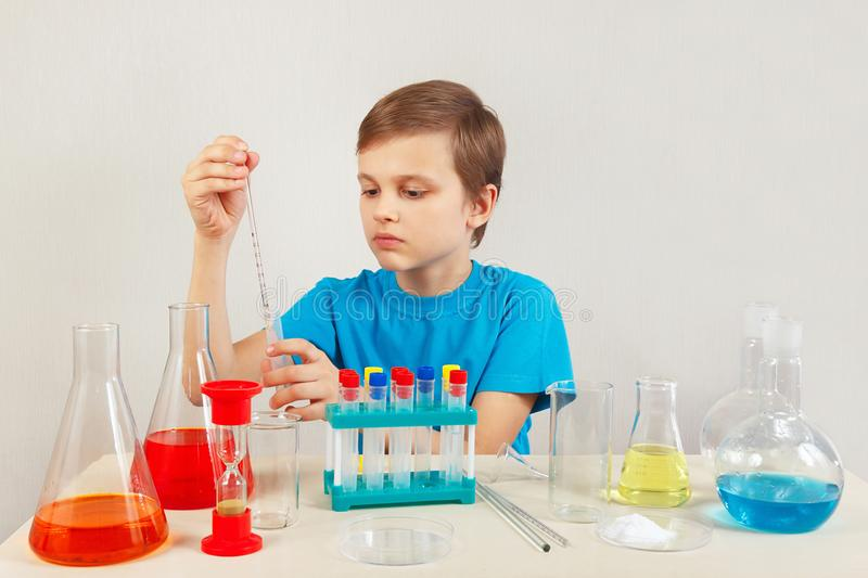 Young smart boy doing chemical experiments in laboratory. Young smart boy doing chemical experiments in the laboratory royalty free stock photo