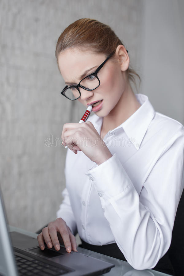 Young smart businesswoman bite pen have problems. On laptop in office royalty free stock photography